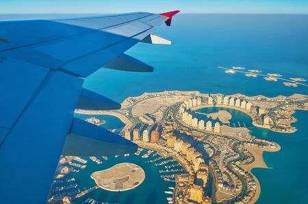 Aerial view on the fantastic landscape and modern architecture of man-made Pearl-Qatar Island and Isola Dana islets' chain, situated at the coast of Doha in Persian Gulf, Qatar