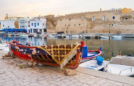 Historical port of Bizertewith a view on medieval Kasbah fortress wall and carcass of old wooden boat on the foreground, Tunisia