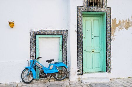 The old wooden door with traditional tile frame and parked vintage motorcycle next to a small door frame, Bizerte, Tunisia