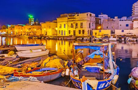 Watch the old fishing boats, docked in port and the line of old houses in bright evening illumination, Bizerte, Tunisia