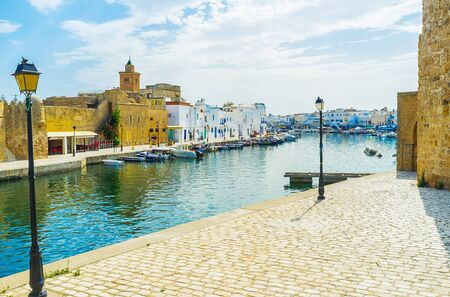 Walk around the old port and enjoy historical architecture of Bizerte, its extant citadels, traditional houses of Arab Medina, fishing boat, moored at shores and vintage lanterns, Tunisia Stockfoto