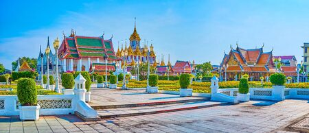 The beautiful Wat Ratchanatdaram complex and King Rama II Memorial Plaza with beautiful flowerbeds on the foreground, Bangkok, Thailand
