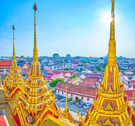The golden spires of Loha Prasat shrine and surrounding old town of Bangkok, with the roofs of residential houses, Thailand