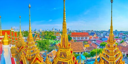 Panorama of scenic golden spires of Loha Prasat shrine, old Bangkoks residential houses with tiled roofs and the silhouette of the skyscrapers of business district on the horizon, Thailand