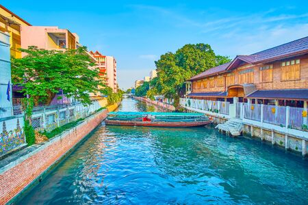 The long passenger boat making a turn in narrow khlong (canal) for sailing in reverse direction in residential district of Bangkok, Thailand 写真素材 - 130155481
