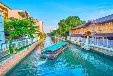 The passenger canal boat maneuvering in narrow canal in Phra Sumen neighborhood, Bangkok, Thailand