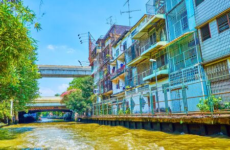 The multi-stored residential houses along the Saen saep Khlong (canal) with bars on the windows, Bangkok, Thailand 写真素材 - 130155552