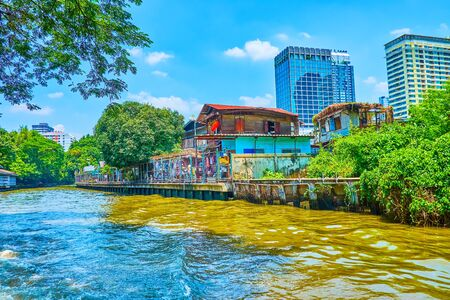 The old timber residential houses along bank of khlongs in Bangkok neighbors with high modern edifices of business districts of the city, Thailand