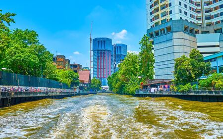 The pleasant boat trip along khlongs of Bangkok observing modern architecture of business districts of new town, Thailand 写真素材 - 130155555