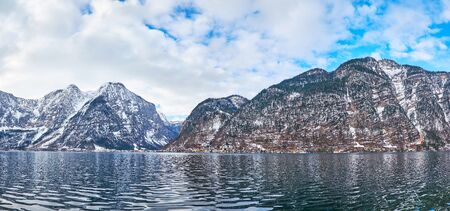 Panorama of Hallstattersee lake with rippled surface and huge Dachstein Alps along its banks, the colorful buildings of Hallstatt town are seen at the foot of Salzberg mount, Salzkammergut, Austria Standard-Bild