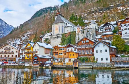 The view on the old houses of Hallstatt and the Parish Church of St Maria Am Berg, located on the top of the hill, Salzkammergut, Austria 写真素材 - 130155805