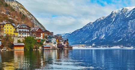 Panorama of Hallstattersee lake with hilly bank of Hallstatt, occupied with wooden cottages and historical edifices, Salzkammergut, Austria 写真素材 - 130155810