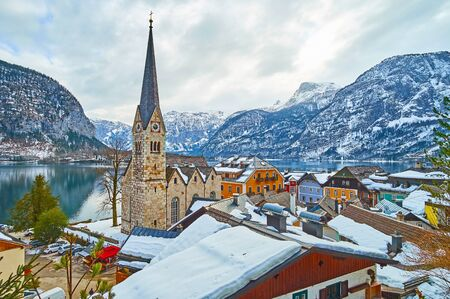 Watch the mirror surface of Hallstattersee lake, rocky Dachstein Alps and tall spire of Parish Church over the old town roofs, Hallstatt, Salzkammergut, Austria