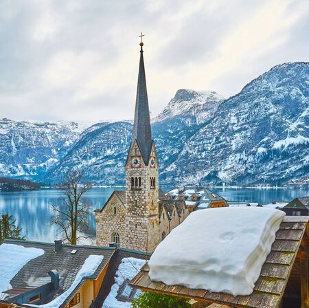 The scenic cityscape of winter Hallstatt with snowy roofs of old townhouses, tall spire of Evangelical Kirche (church), calm surface of Hallstattersee lake and rocky slopes of Dachstein Alps, Austria
