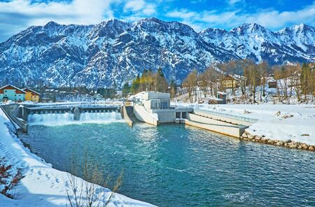 The snowy banks of Traun river with a view on dam with two fish passes (fischtreppe) on the sides and rocky Dachstein Alps on the background, Salzkammergut, Austria 写真素材 - 130155881