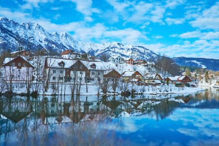 The snowbound housing of Bad Goisern is reflected on mirror surface of Traun river, Salzkammergut, Austria Reklamní fotografie
