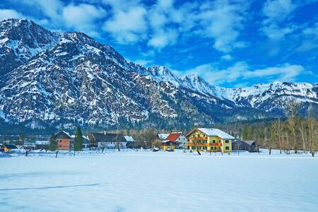 The winter morning in Bad Goisern with a view on snowbound meadow, line of houses and huge Dachstein mountains on background, Salzkammergut, Austria 写真素材 - 130155883