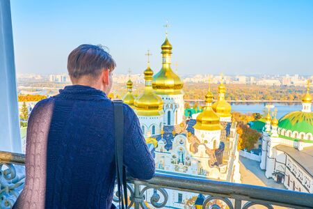 The tourist observing the landmarks Kiev Pechersk Lavra complex from the viewpoint of the Great Bell Tower, Kiev, Ukraine 写真素材 - 130156042
