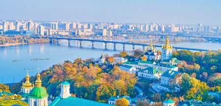 Bell tower of Kiev Pechersk Lavra overlooks Dnieper river with bridges across it and Church of the Nativity of the Blessed Virgin Mary, located on territory of Lower (Far) Caves of Monastery, Ukraine. 写真素材 - 130156201