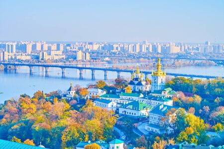 Observe the foggy Dnieper river with its bridges, autumn greenery along the banks and Church of the Nativity of the Blessed Virgin Mary of Lower (Far) Caves of Kiev Pechersk Lavra Monastery, Ukraine. 写真素材 - 130156202