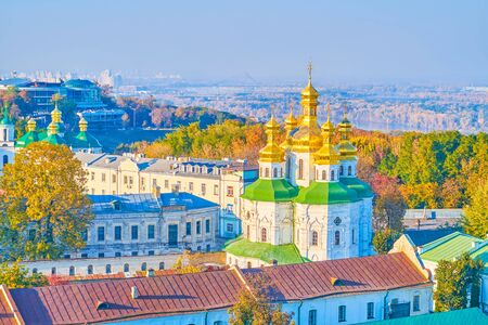 The foggy skyline with a view on All Saints church of Kiev Pechersk Lavra monastery, lush forests, covering the city hills, Dnieper river and Northern (Pivnichnyi, former Moskovsky) bridge, Ukraine. 写真素材 - 130156298