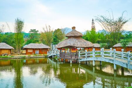 Walk along the scenic pond with wooden bridge and watch traditional houses of Santichon Chinese Yunnan cultural village, located in mountains next to Pai, Thailand 写真素材 - 130157034