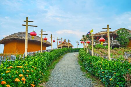 The ascent, leading to the Yun Lai viewpoint, with rows of Chinese lanterns, flower beds, traditional houses with palm leaf roofs, Santichon tea village, Thailand