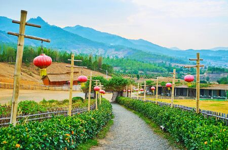 Walk the alley, decorated with flower beds, red Chinese lanterns on tall bamboo poles with scenic wooden gate at the end, Yun Lai viewpoint, Santichon tea village, Thailand