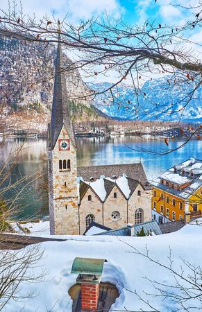 Old town walk with a view on Evangelical Church building, seen through the tree branches and snowy roofs of Halltatt, Salzkammergut, Austria 写真素材 - 130157362