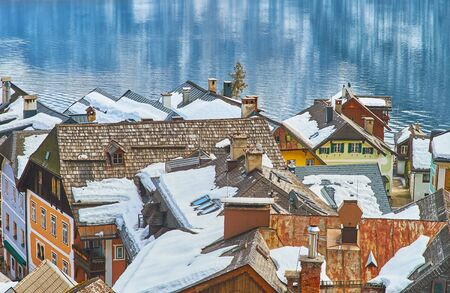 The densely located snowy roofs of old Hallstatt houses with a view on Hallstattersee lake, reflecting rocky Dachstein Alps, Salzkammergut, Austria Imagens