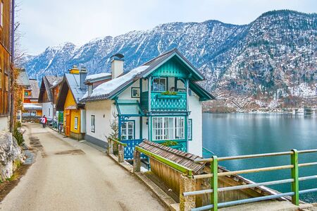 The old town street, located on the mountain slope, lined with traditional Alpine houses and has a viewing platform, observing Hallstattersee lake, Halltatt, Salzkammergut, Austria 写真素材