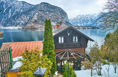 The old wooden houses with scenic hilly gardens on the bank of Hallstattersee lake, Halltatt, Salzkammergut, Austria 写真素材 - 130157397