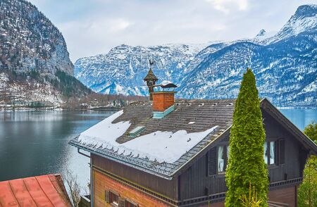 The view on snowy Dachstein Alps and dark waters of Hallstattersee lake behind the old house roof with a chimney and vintage weather vane with bell and figurine of rooster, Halltatt, Salzkammergut, Austria 写真素材 - 130157398