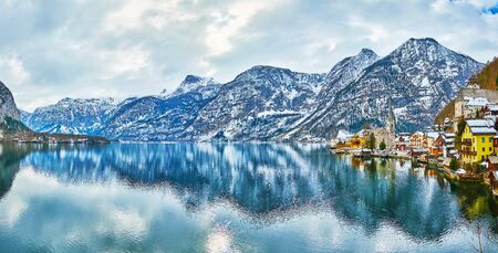Panorama of the old town of Hallstatt with a view on Halstattersee lake, tall spire of Evangelical Parish Church, colorful houses and Dachstein Alps on the background, Salzkammergut, Austria.