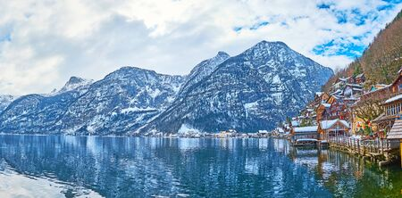 Panorama of rippled Hallstattersee lake from Halltatt town embankment, observing Dachstein Alps and cloudy sky, reflecting in lake waters, Salzkammergut, Austria 写真素材