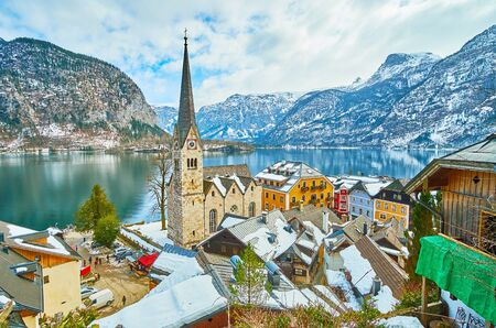 Hallstatt town center with a view on Evangelical Church, old townhouses, embankment of Hallstatter see (lake) and snowy Dachstein Alps on the background, Salzkammergut, Austria. 写真素材 - 130157764
