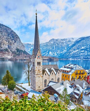 Evangelical church with tall spire on the clock tower is the architectural symbol and one of the most known landmarks of Halltatt, situated on the bank of Hallstattersee lake, Salzkammergut, Austria 写真素材 - 130157765