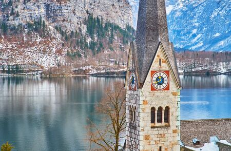 The surface of Hallstattersee lake and Dachstein Alps with the clock tower of Evangelical church of Halltatt on the foreground, Salzkammergut, Austria 写真素材 - 130157766