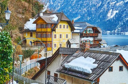 Walk the streets of old town and watch its old houses, green Salzberg mountain slopes and Hallstattersee lake behind the snowy roofs, Halltatt, Salzkammergut, Austria 写真素材 - 130157767