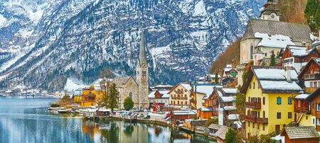 The bank of Hallstatter see is occupied with dense colorful houses, stone Evangelical church with tall spire and snowy Dachstein Alps on background, Hallstatt, Salzkammergut, Austria. 写真素材 - 130157788