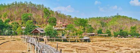 Panorama of mountain scenery of Pai suburb with dried paddy field and old Boon Ko Ku So bamboo bridge, Thailand Zdjęcie Seryjne - 130157909