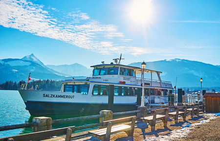 ST WOLFGANG, AUSTRIA - FEBRUARY 23, 2019: The ferry is moored at the bank of Wolfgangsee lake, surrounded by snowy Alps of Salzakmmergut, on February 23 in St Wolfgang 写真素材 - 130138247