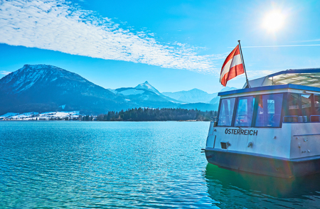 ST WOLFGANG, AUSTRIA - FEBRUARY 23, 2019: Bright blue rippled surface of Wolfgangsee lake with waving Austrian flag on the ferrys stern and rocky Alps on opposite bank, on February 23 in St Wolfgang