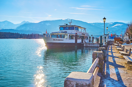 ST WOLFGANG, AUSTRIA - FEBRUARY 23, 2019: Relax in small park on embankment of Wolfgangsee lake with small benches, old-styled streetlights and ferry port on background, on February 23 in St Wolfgang 写真素材 - 130138270