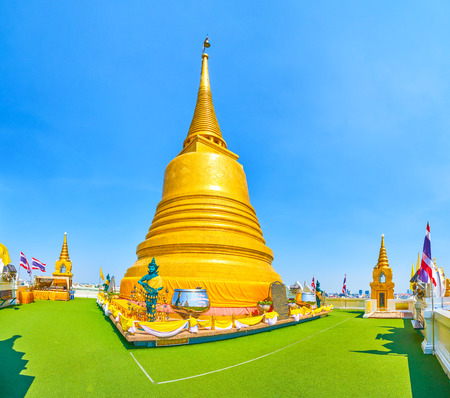 BANGKOK, THAILAND - APRIL 24, 2019: The beautiful golden Chedi on the top of Wat Saket (Golden Mount) Temple and walking courtyard  with small ones on the perimeter, on April 24 in Bangkok