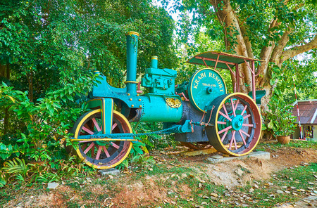AO NANG, THAILAND - APRIL 25, 2019: The colorful vintage locomotive with welcome board of Krabi resort, standing in lush greenery of park, on April 25 in Ao Nang Editöryel