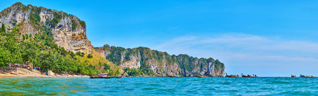 AO NANG, THAILAND - APRIL 25, 2019: Panorama of Ao Nang rocky coastline with a view on sand beach and lush tropical greenery on the foreground, on April 25 in Ao Nang