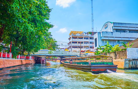 BANGKOK, THAILAND - APRIL 24, 2019: The old passenger ferry fast sails along the Saenseap khlong in old town making high waves, on April 24 in Bangkok Editorial