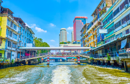 BANGKOK, THAILAND - APRIL 24, 2019: The Saensaep khlong leads through modern district of the city with residential houses,  numerous bridges and high buildings built on its the banks, on April 24 in Bangkok