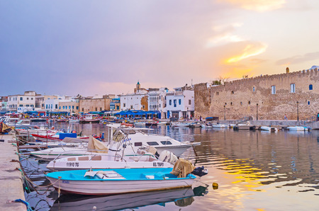 BIZERTE, TUNISIA - SEPTEMBER 4, 2015: The city walk on sunset with a view on row of moored fishing boats, old houses and wall of Kasbah fortress, on September 4 in Bizerte